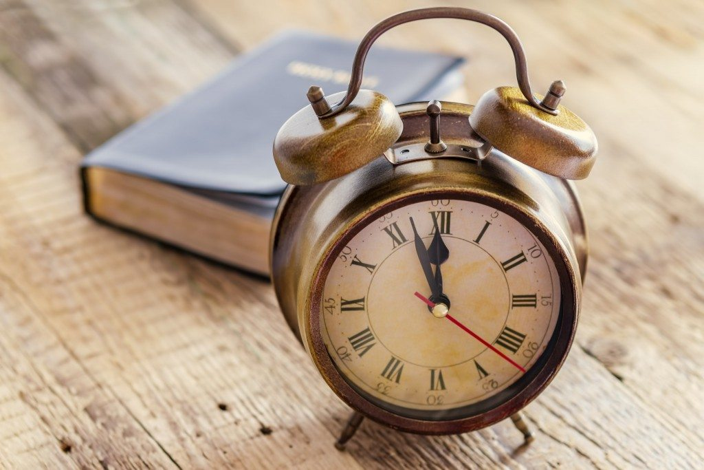 bigstock-Clock-and-Bible-on-Wood-65642575